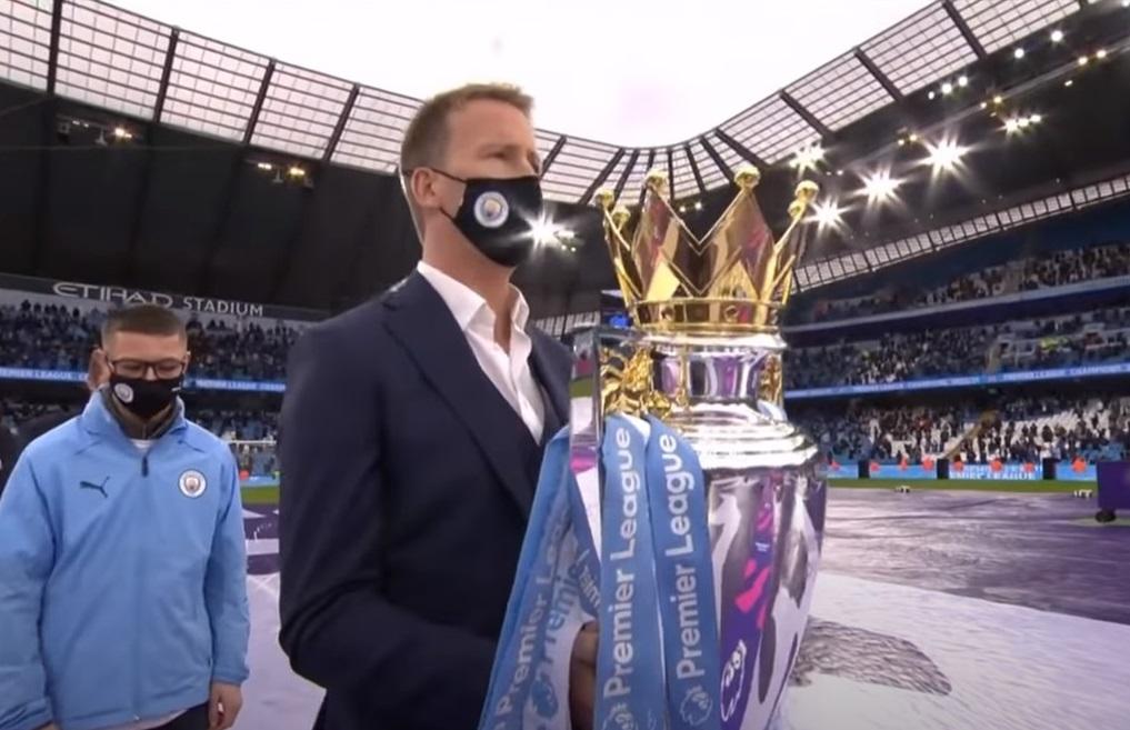 Dr Jon Bell carrying the Premier League Trophy