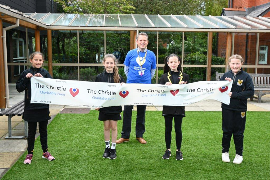 Year Six pupils with The Christie banner